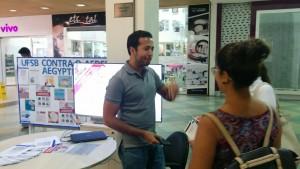 Com o mural da UFSB e o telão ao fundo, um servidor da UFSB sorri enquanto repassa informações sobre a campanha para duas visitantes do shopping