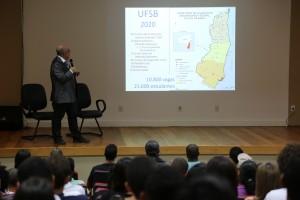 Em um palco com piso de madeira clara e com parede de fundo também clara, o professor Antonio cardoso apresenta uma projeção com o mapa de abrangência da UFSB e a expectativa de alunos e cursos em 2020